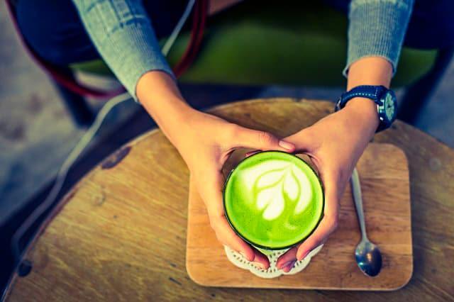 Hände halten eine Schale mit Matcha Latte