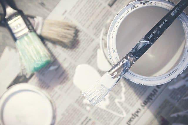 Farbeimer mit Pinseln auf Zeitungsunterlage