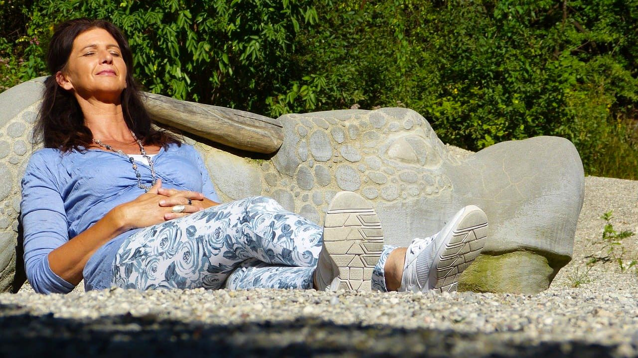Frau genießt Sonne auf einer Bank
