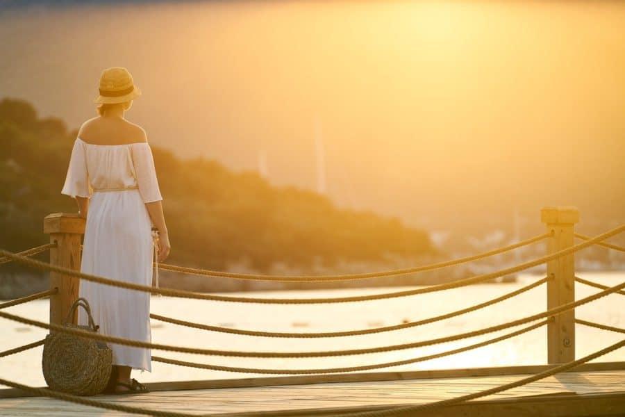 Frau im Urlaub auf einer Brücke bei Sonnenuntergang